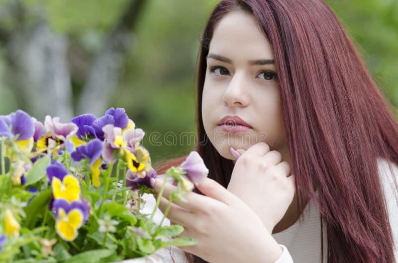 Cabelo vermelho bonito que senta-se em uma tabela de madeira do jardim fotografia de stock