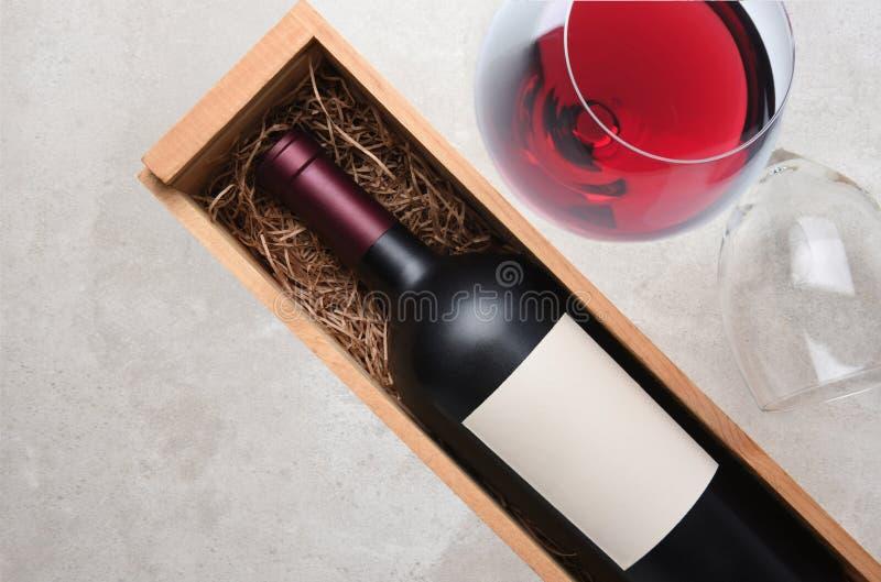 Cabernet - sauvignon: En flaska i träfall med ett exponeringsglas av röda wi royaltyfri bild