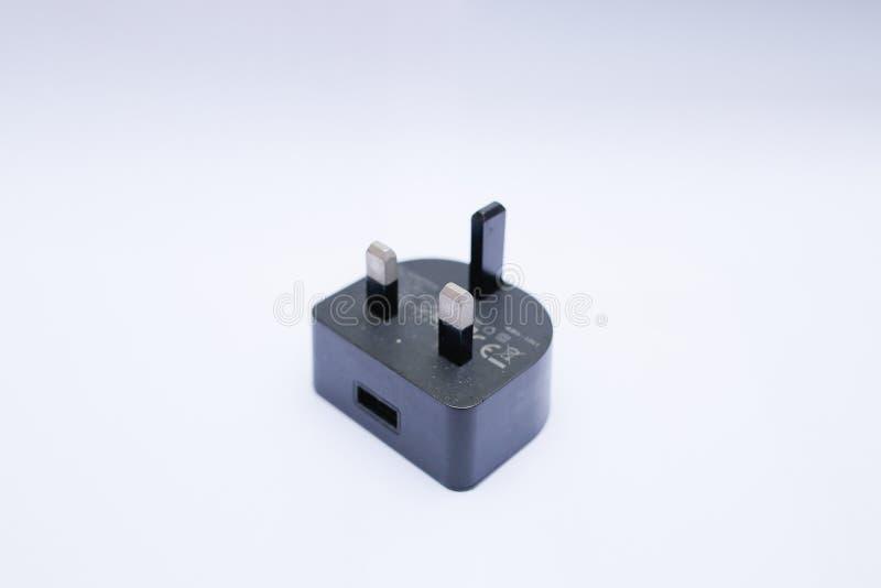 Cabeza/adaptador negros del cargador USB en un fondo blanco imagenes de archivo