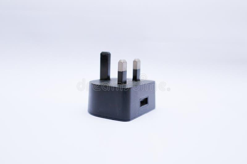 Cabeza/adaptador negros del cargador USB en un fondo blanco fotografía de archivo