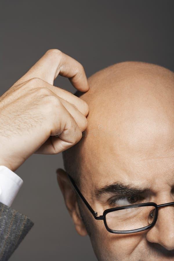 Cabeza calva cosechada de In Glasses Scratching del hombre de negocios imágenes de archivo libres de regalías