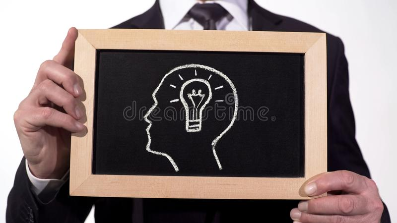 Cabeza de la bombilla dibujada en la pizarra en manos del hombre de negocios, idea creativa del negocio imágenes de archivo libres de regalías