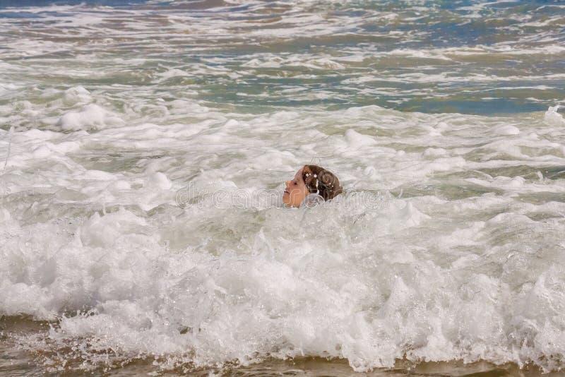 Cabeza de la chica joven en olas oceánicas bajas foto de archivo libre de regalías