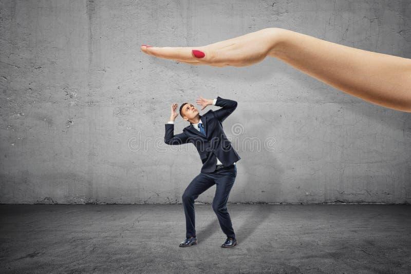 Cabeza de la cubierta del pequeño hombre de negocios con las manos y el mirar para arriba la mano de la mujer grande sobre listo  foto de archivo libre de regalías