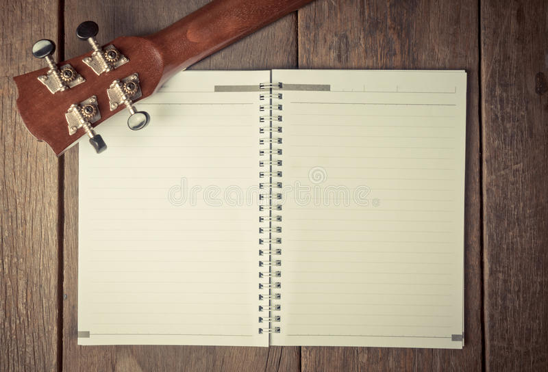 Cabeza de la guitarra en el libro para la escritura de la canción imagenes de archivo