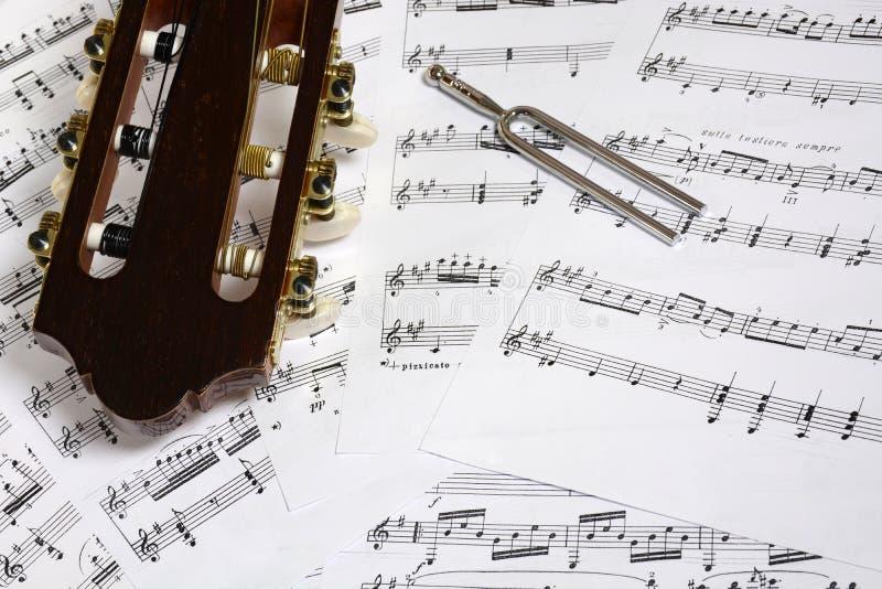 Cabeza de la guitarra y primer del diapasón en notas fotografía de archivo