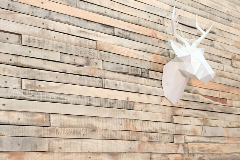 Cabeza de los ciervos hecha del papel en una pared de listones de madera Visión en ángulo Fondo del diseñador para la decoración  imagen de archivo