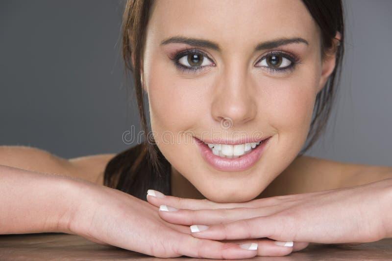 Cabeza de reclinación femenina triguena joven emocionada en Headshot de las manos imagen de archivo