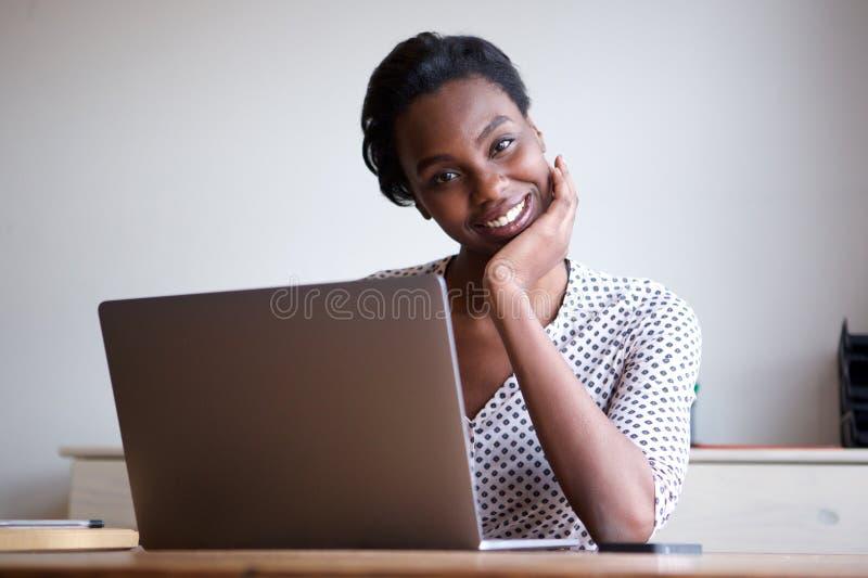 Cabeza de reclinación de la mujer a mano que se sienta en el escritorio con el ordenador portátil imagen de archivo libre de regalías