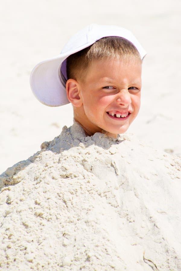 Cabeza de un muchacho en el casquillo enterrado en la arena imagen de archivo