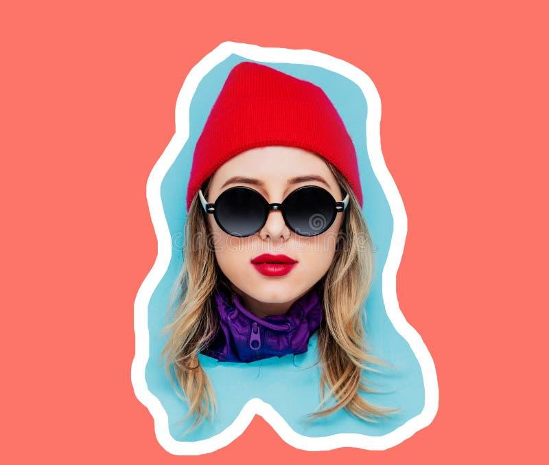 Cabeza de una muchacha joven del estilo en casquillo y gafas de sol en fondo coralino azul y vivo del color foto de archivo