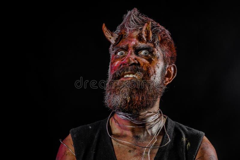 Cabeza del demonio de Halloween con los ojos asustadizos y cuernos sangrientos fotos de archivo