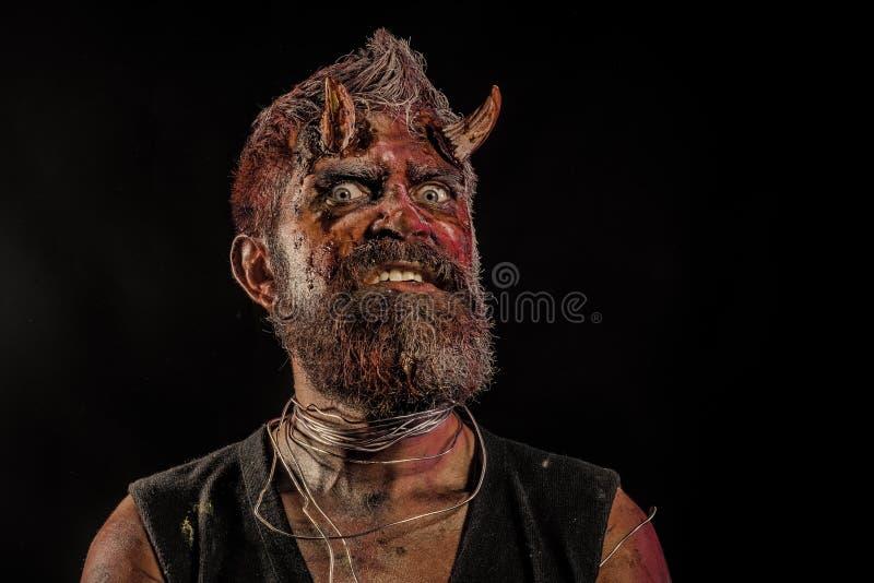 Cabeza del demonio de Halloween con los ojos asustadizos y cuernos sangrientos fotografía de archivo