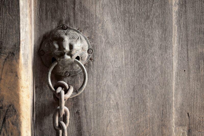 Cabeza del león como manija del metal del golpeador en una puerta de madera vieja fotos de archivo