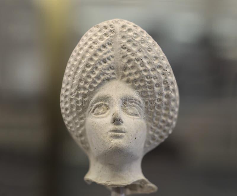 Cabeza femenina de la estatuilla de la terracota con el tocado complicado triangular foto de archivo libre de regalías