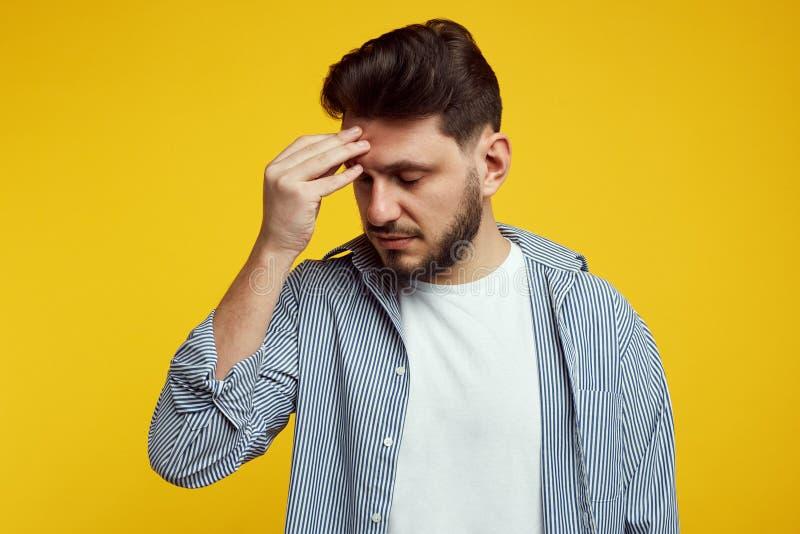 Cabeza joven triste y trastornada de la tenencia del muchacho abajo y pensando en trabajo Hombre barbudo en la camisa sport aisla imagenes de archivo