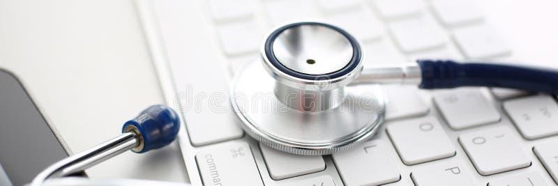 Cabeza médica del estetoscopio que miente en el teclado de plata en la mesa de trabajo de la oficina del doctor foto de archivo