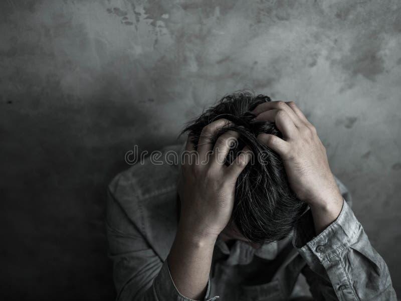 Cabeza que se sienta del hombre de negocios triste en manos en el dormitorio oscuro con el ambiente de la luz corta, concepto dra foto de archivo