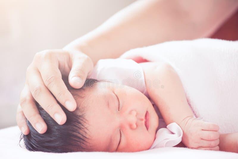 Cabeza recién nacida asiática conmovedora del bebé de la mano de la madre imagen de archivo