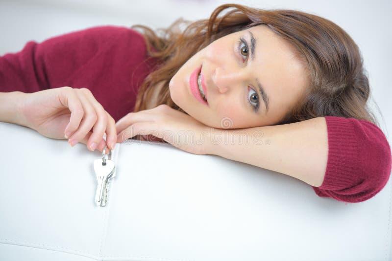 Cabeza relajante de la chica joven linda en el sofá que lleva a cabo llaves imágenes de archivo libres de regalías