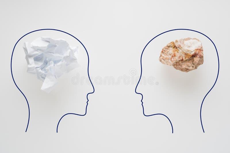 Cabezas de dos personas con forma de papel arrugada del cerebro y la forma de piedra del cerebro Dos personas con diverso pensami foto de archivo libre de regalías