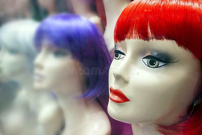 Cabezas del maniquí con las pelucas coloridas imagenes de archivo