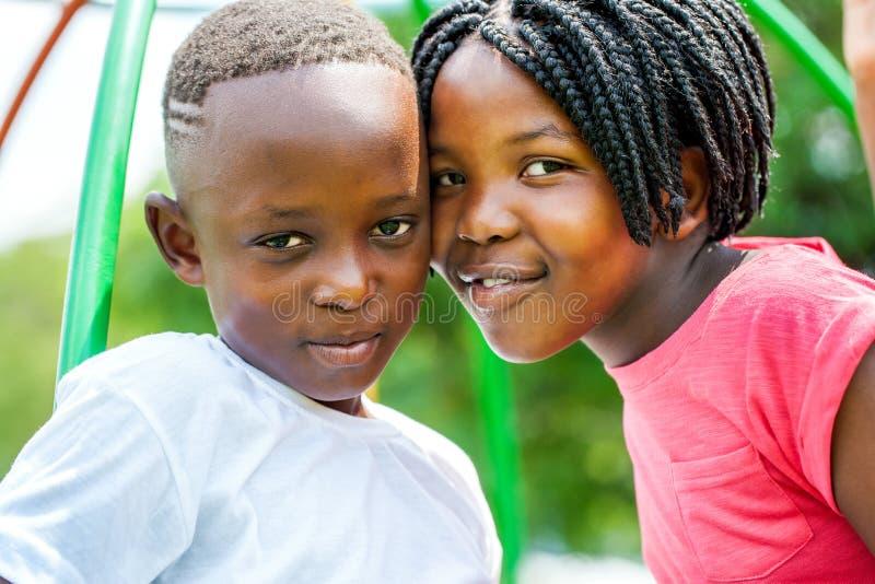 Cabezas que se unen a africanas jovenes del hermano y de la hermana al aire libre imágenes de archivo libres de regalías