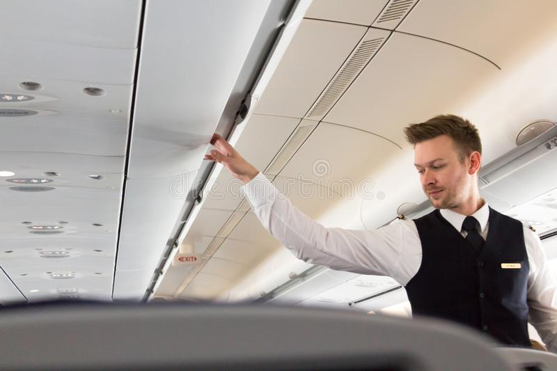 Cabin crew checking checking the overhead compartments. Munich, Germany - September 21th, 2017: A male Flight attendant is checking the overhead compartments of royalty free stock photography