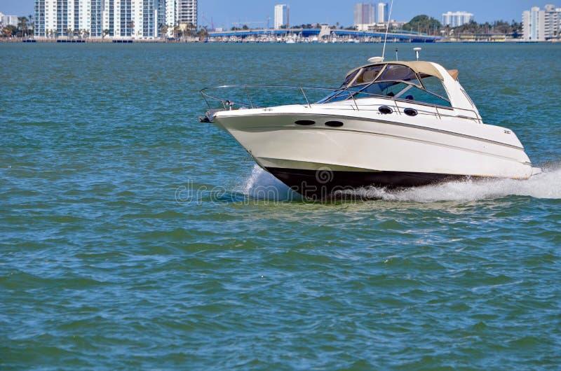 Cabin Cruiser on the Florida Intra-coastal Waterway. A white cabin cruiser on the florida intra-coastal waterway off Miami Beach with a causeway bridge and Miami stock photos