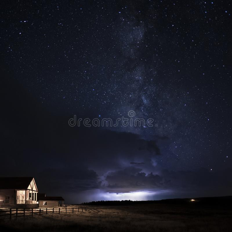 A lightning storm passing through Zion under the Milky Way with a cabin and field in the foreground royalty free stock photography