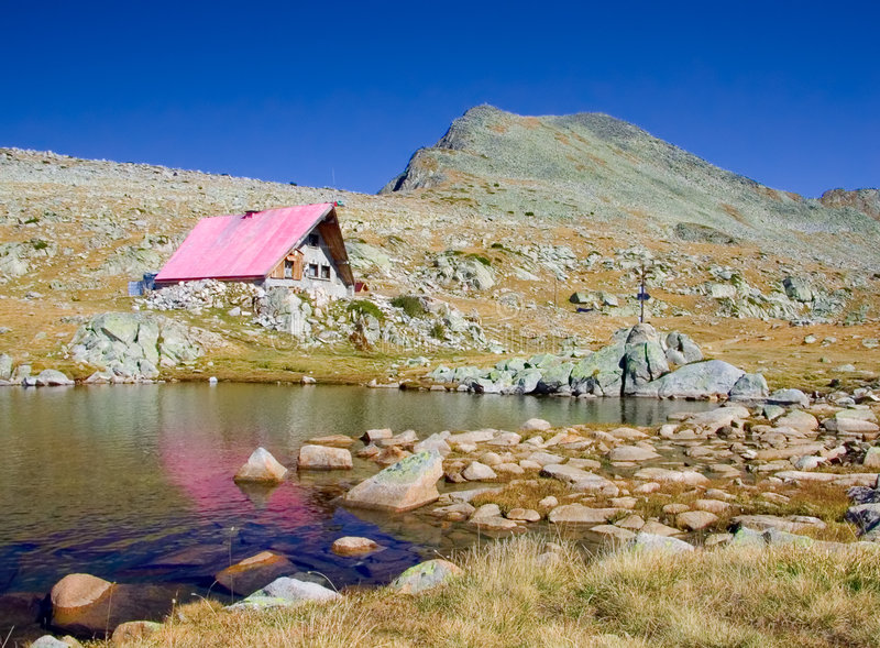 Cabin and a glacial lake up in national park Pirin, Bulgaria stock photography