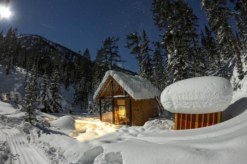 Cabin house chalets in winter forest with snow in light moon and. Starry sky royalty free stock photography