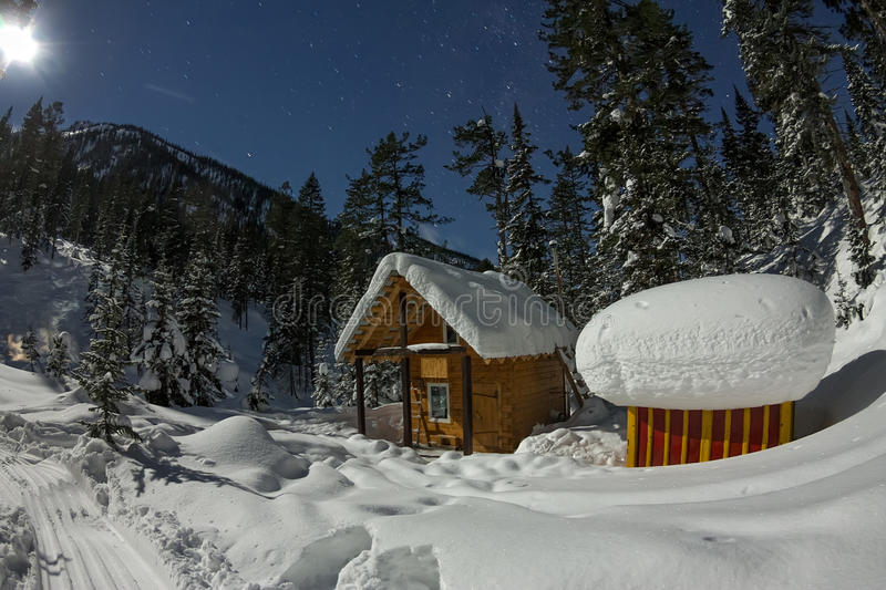 Cabin house chalets in winter forest with snow in light moon and. Starry sky royalty free stock photos