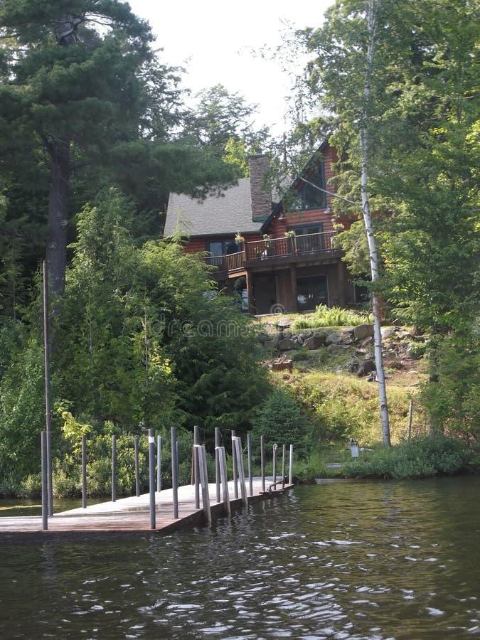 Cabin on lake flower stock images