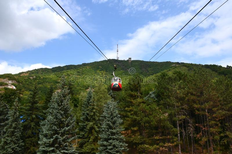 The cabin moves along the cable car up the mountain above the fo royalty free stock photos