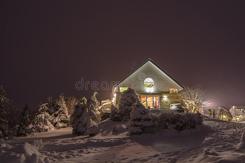 Cabin in the snow between snowcovered pine trees. Cabin with lights on in the snow between snow covered pine trees in the evening royalty free stock images