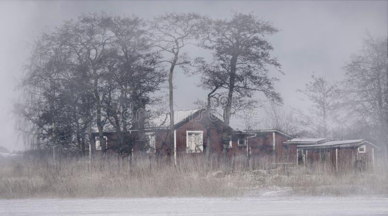 Cabina abandonada en el medio de un lago congelado La niebla densa cubre el aire foto de archivo