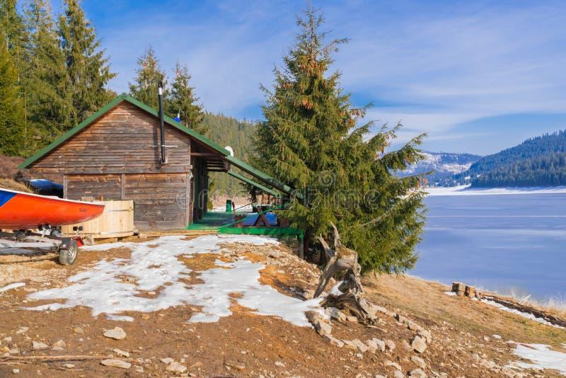 Cabina cerca de un lago congelado en una montaña fotografía de archivo libre de regalías