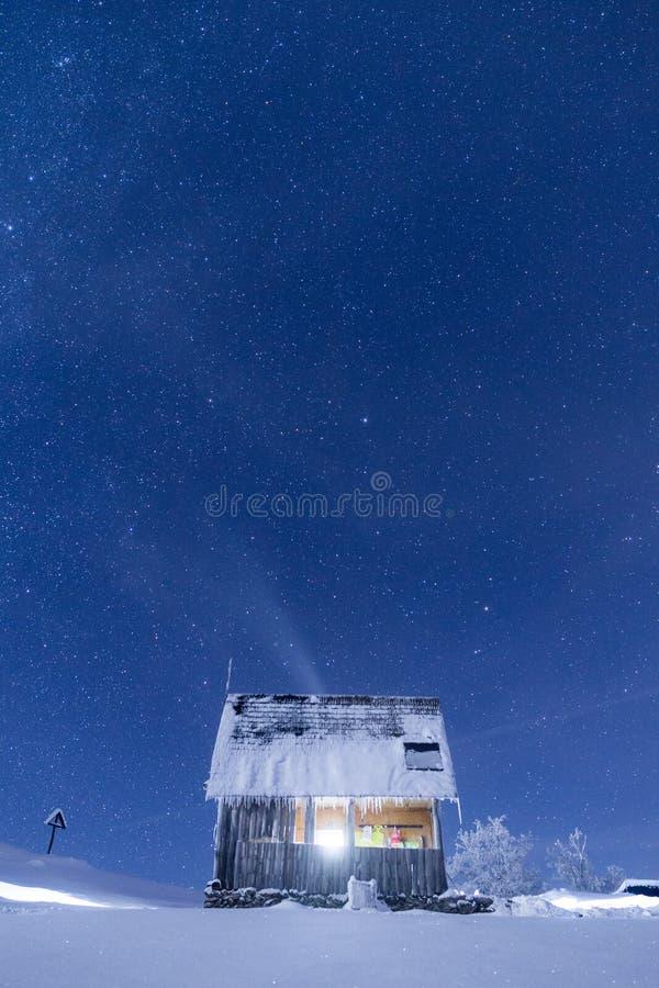Cabina congelada de las montañas debajo de un cielo nocturno llenado de las estrellas fotos de archivo libres de regalías