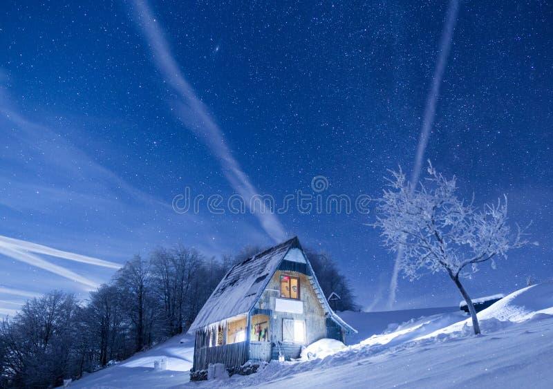 Cabina congelada de las montañas debajo de un cielo nocturno llenado de las estrellas imagenes de archivo