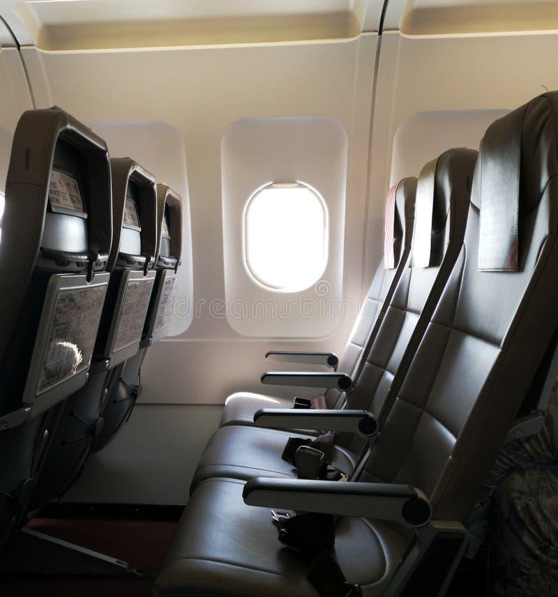 Cabina de la ventana del aeroplano con los sitios vacíos imagen de archivo