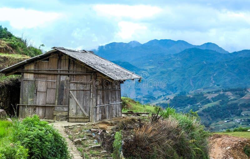 Cabina de madera de la choza en cielo del claro de la montaña imagen de archivo