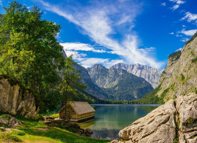 Cabina de madera en costa idílica contra las montañas y el wonde alpinos imágenes de archivo libres de regalías