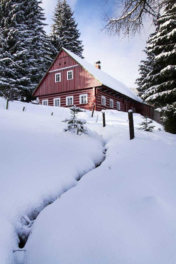 Cabina de madera roja en un país nevoso escarchado foto de archivo