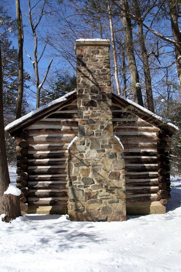 Cabina de registro colonial en nieve foto de archivo