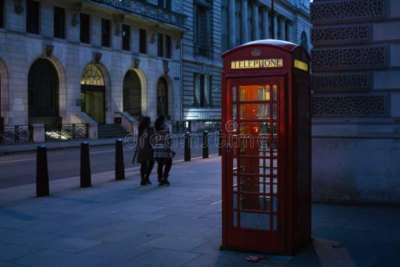 Cabina de teléfonos roja británica tradicional en la calle de Londres, iluminada en de lado en la noche fotografía de archivo libre de regalías