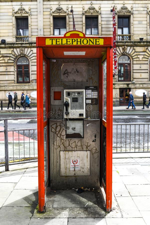 Cabina de teléfonos roja sucia en el centro de ciudad en Inglaterra foto de archivo