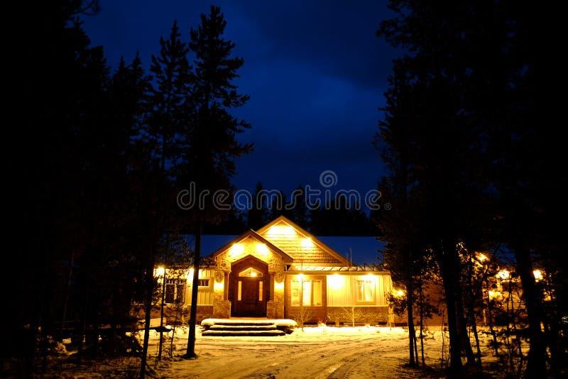 Cabina del invierno en la noche con nieve y luces que brillan intensamente calientes imagenes de archivo