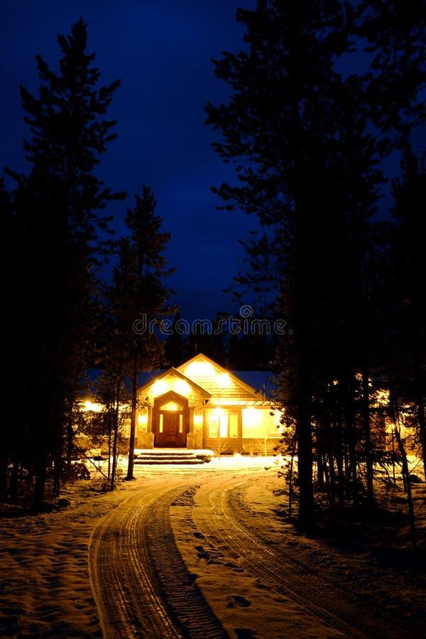 Cabina del invierno en la noche con nieve y luces que brillan intensamente calientes fotos de archivo