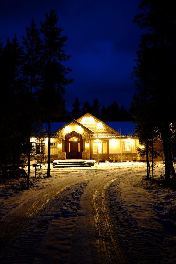 Cabina del invierno que brilla intensamente caliente en el cielo azul de la noche fotos de archivo libres de regalías